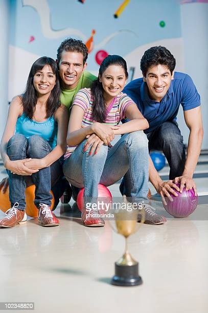 Two young couples with bowling balls and a trophy in a bowling alley