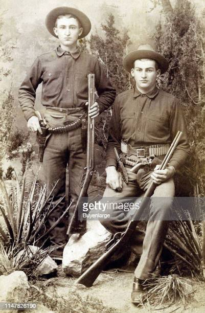 Two Young Cowboys 'Guns Bowie Knives Rifles' Two Cowboys Have All The Accouterments For The Wild West Over And Under Shotgun Bowie Knife Cartridge...