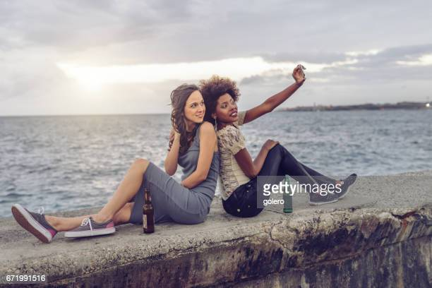 two young cuban woman taking selfie on balustrade of Malecon in Havanna
