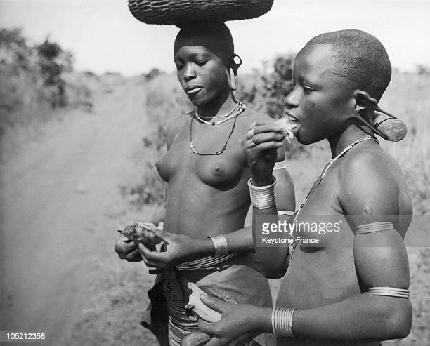Two Young Daughters Of A Tribe Near Lake Victoria In Tanzania Uganda Or Kenya Eat Fruit On The Side Of The Road In The 1940S Note The Hole In The...