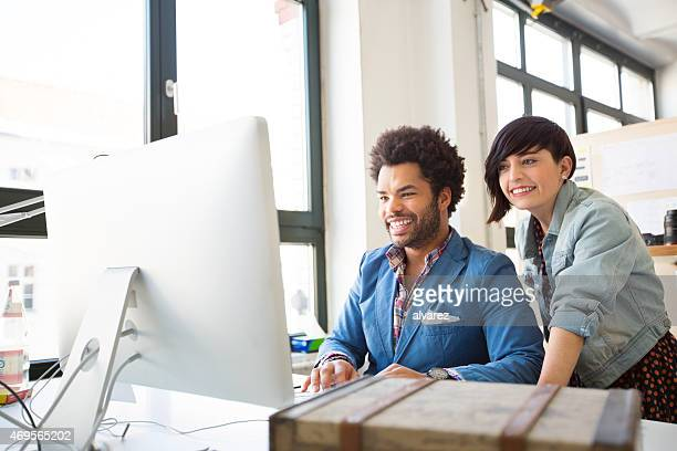 Two young designers working on a pc