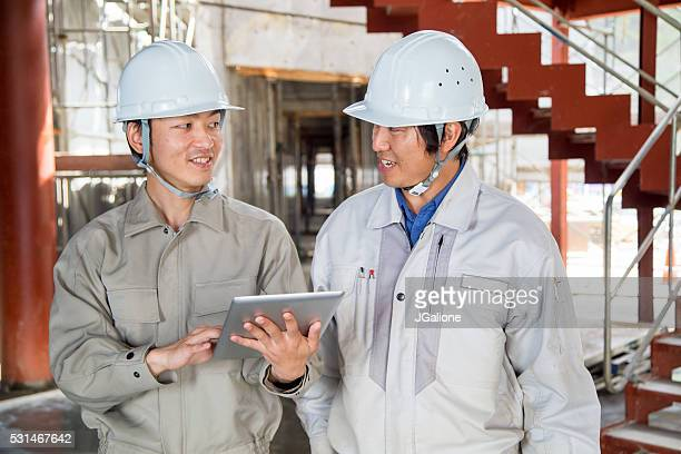 Two young engineers looking at a digital tablet