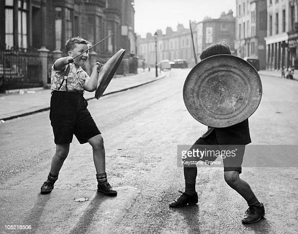 Two Young English Boys Practice SwordFighting On Play Street In London Around 1947 2 Years After The End Of The War They Enjoy A Newfound Insouciance