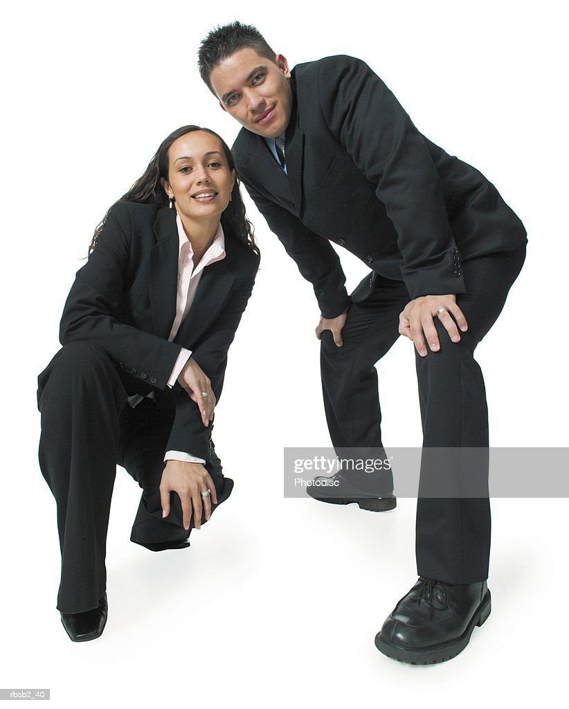 two young ethnic business people crouch down and smile at the camera : Foto de stock