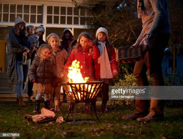 Two young families standing around a fire