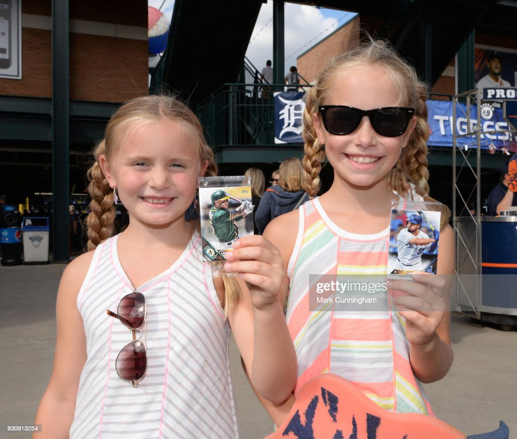 Two young fans hold up their Topps baseball cards which were given out to fans to celebrate National Baseball Card Day prior to the game between the Detroit Tigers and the Minnesota Twins at Comerica Park on August 12, 2017 in Detroit, Michigan. The Tigers defeated the Twins 12-11.