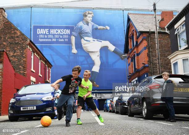 Two young fans play football outside the stadium prior to the Premier League match between Everton and Chelsea at Goodison Park on April 30 2017 in...