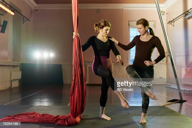 Two young female aerial acrobats practicing by silk rope