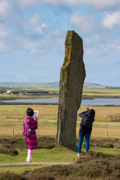 Two young female Asian visitors with iPad and camera photograph The Ring of Brodgar circle of Neolit