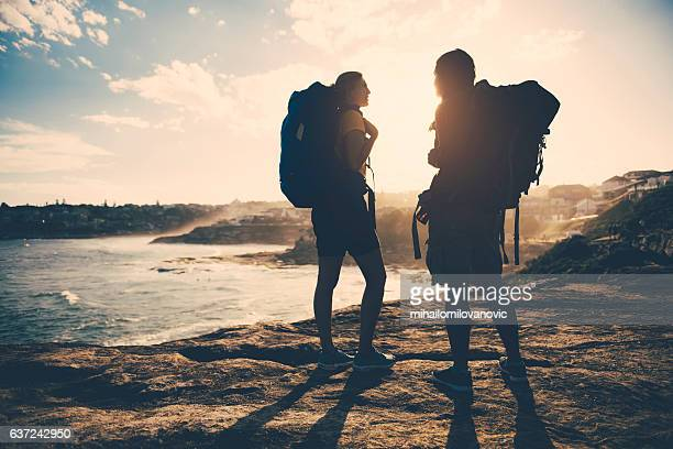 Two young female backpackers exploring coastline