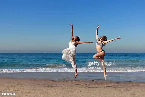 Two young female dancers leaping mid air on beach