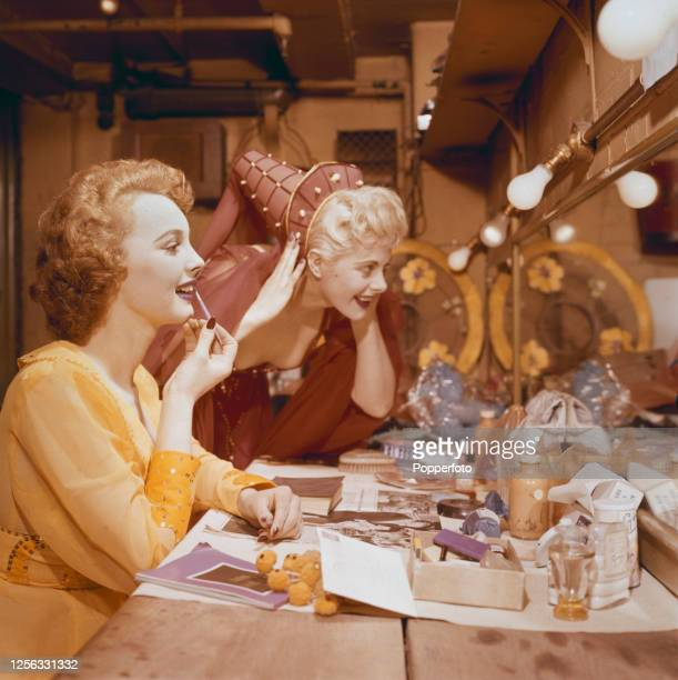 Two young female dancers or Windmill girls apply makeup and lipstick in a dressing room backstage prior to performing on stage at the Windmill...