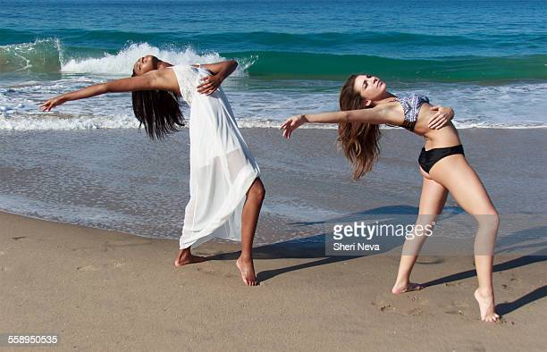 Two young female dancers poised bending backwards on beach
