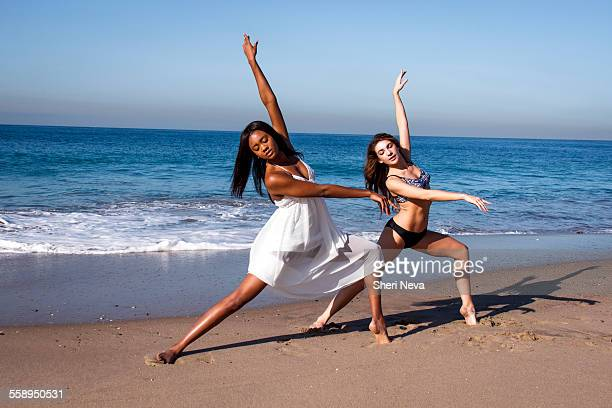 Two young female dancers poised with arms raised on beach