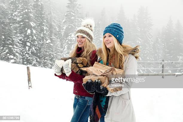 Two young female friends carrying logs in snowy mist