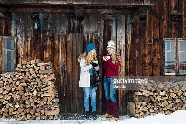 Two young female friends chatting outside wooden cabin
