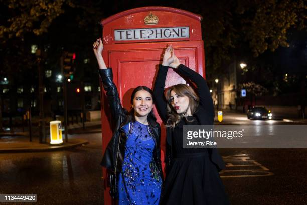 two young female friends dancing in front of red phone box at night, london, uk - telephone box stock pictures, royalty-free photos & images