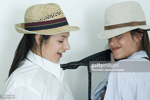 two young female friends dressed in button down shirts, ties and hats, one pulling on the other's tie, portrait - like button stockfoto's en -beelden