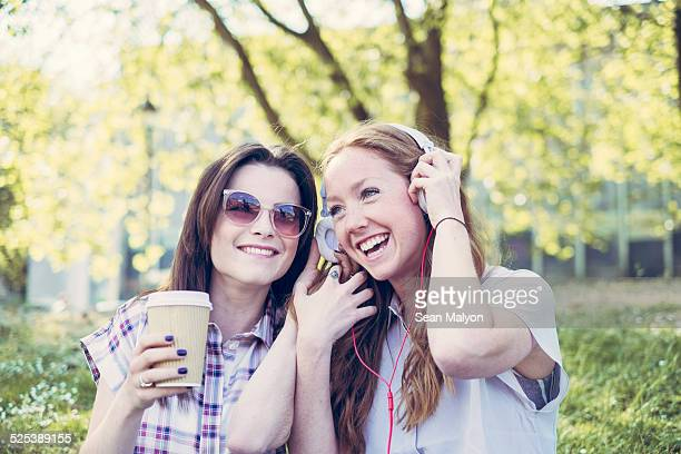 Two young female friends drinking coffee and listening to music on headphones in park