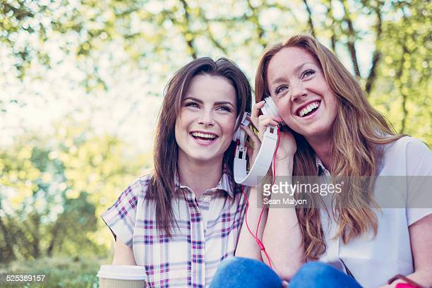 Two young female friends drinking coffee and sharing music on headphones in park