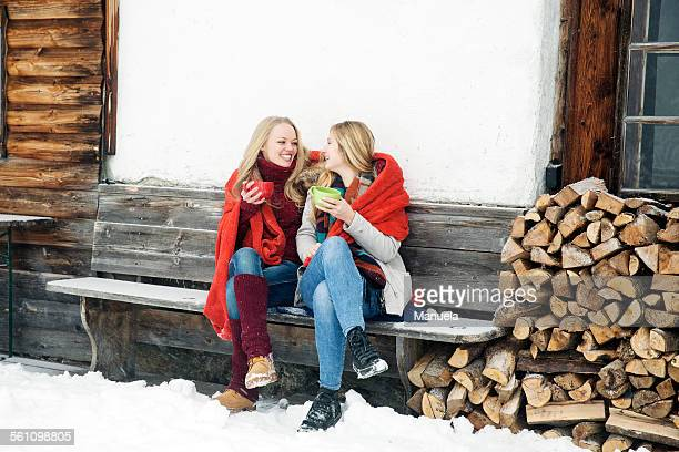 two young female friends drinking coffee outside wooden cabin - レッグウォーマー ストックフォトと画像