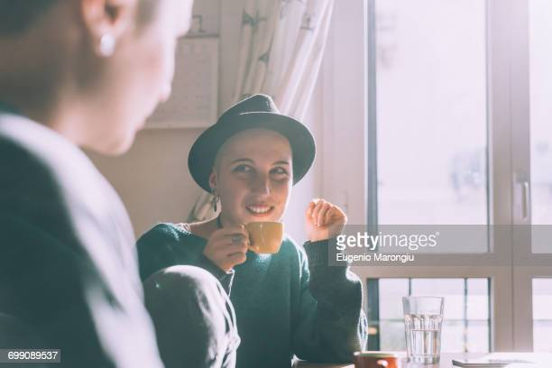 Two young female friends drinking espresso in kitchen