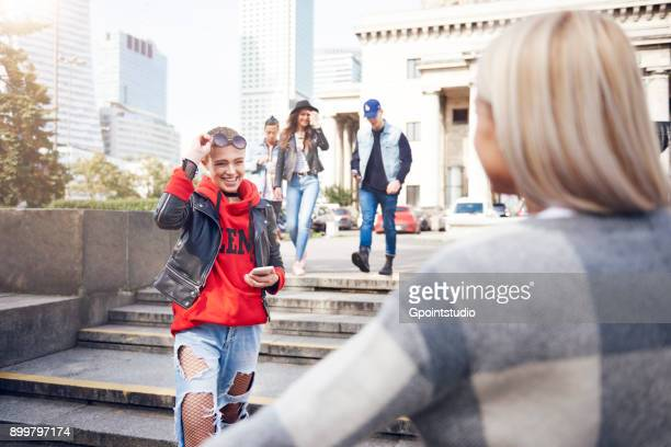 Two young female friends greeting each other in city