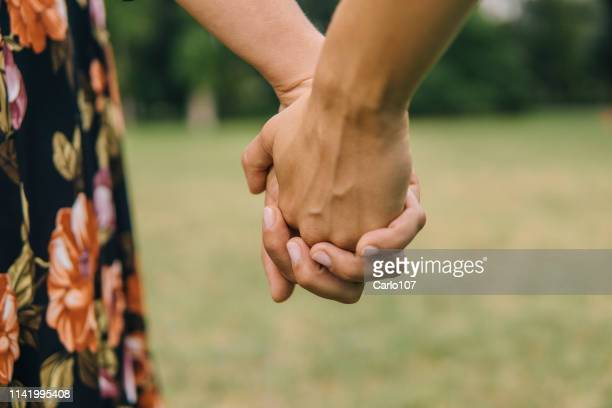 two young female friends holding their hands outdoor in springtime - civil partnership stock pictures, royalty-free photos & images