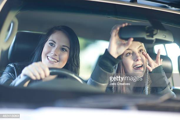 Two young female friends in car