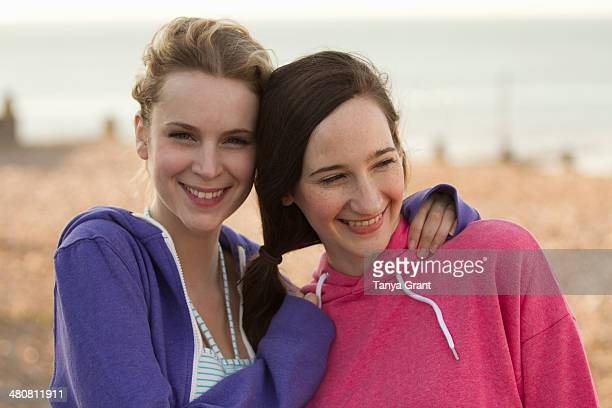 Two young female friends on beach at Whitstable, Kent, UK