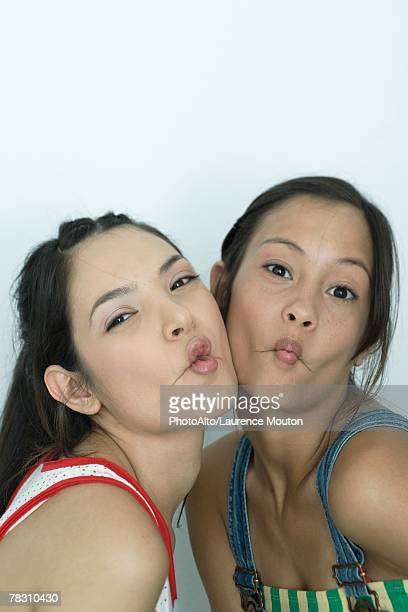 Two young female friends puckering lips, looking at camera, portrait