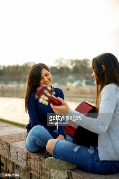Two young female friends sitting by the river,singing and playing guitar