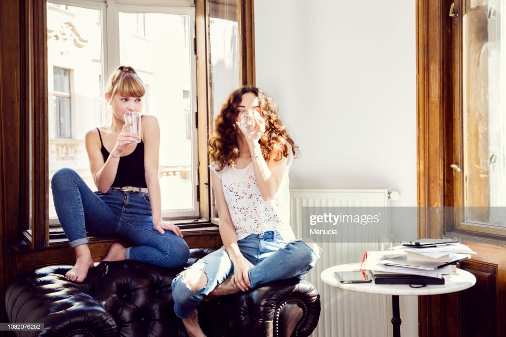 Two young female friends sitting on living room armchair drinking water : Stockfoto