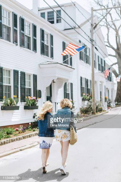 two young female friends strolling along village road, rear view, menemsha, martha's vineyard, massachusetts, usa - marthas vineyard stock pictures, royalty-free photos & images