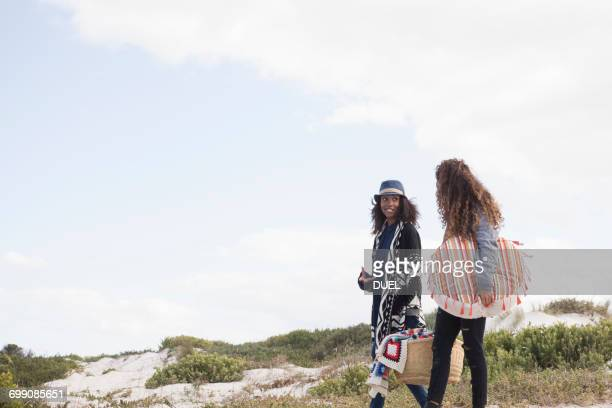 Two young female friends strolling on beach, Western Cape, South Africa