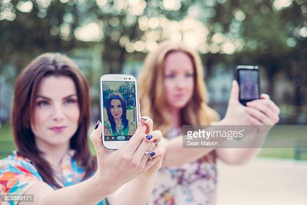 Two young female friends taking selfie on smartphones in unison
