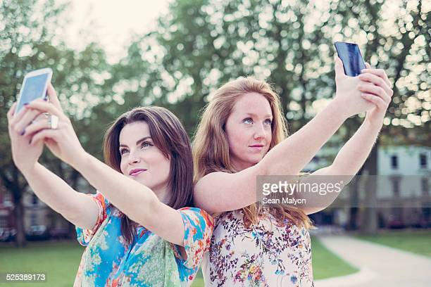 two young female friends taking selfie on smartphones side by side - sean malyon stock pictures, royalty-free photos & images