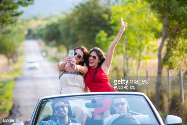 Two young female friends taking selfie whilst driving on rural road in convertible, Majorca, Spain