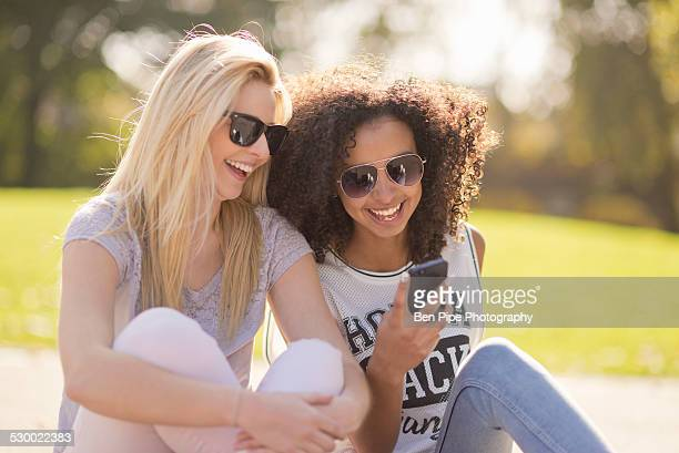 Two young female looking down at text message on smartphone in park