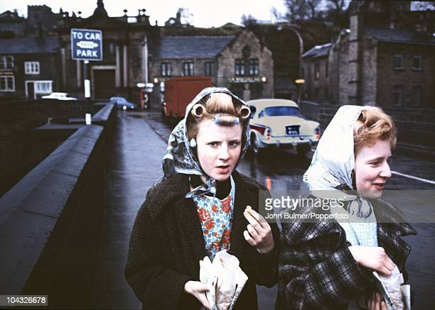 Young women snacking in the street in Elland a town in Calderdale West Yorkshire circa 1977
