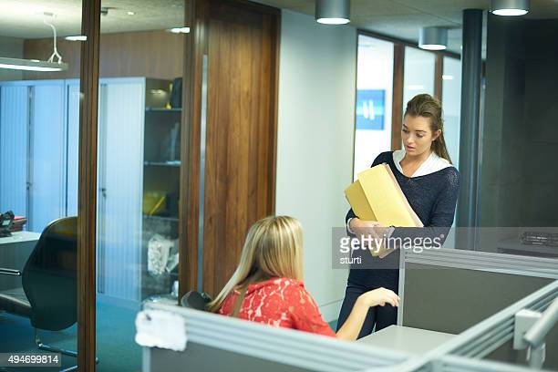 two young female office workers chatting