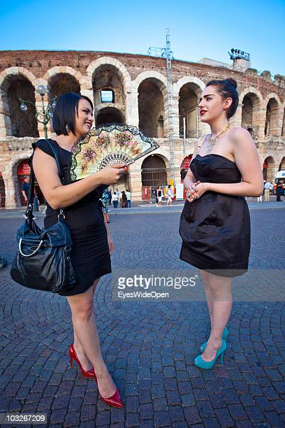Two young female opera-goers with black evening dresses and high heels in front of the Arena of Verona on July 14, 2010 in Verona, Italy. The famous...