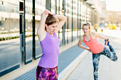 Two young female runners warming up in city