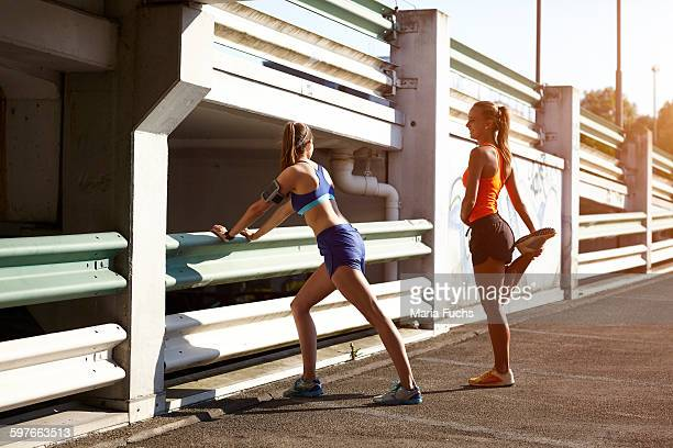 Two young female runners warming up in parking lot