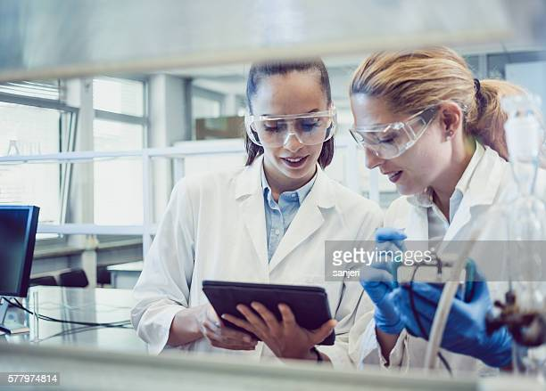 Two Young Female Scientists Looking at the PC tablet