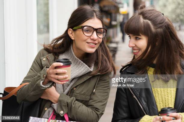 Two young female shoppers chatting while strolling on street with takeaway coffee