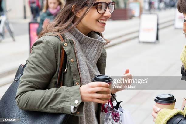 two young female shoppers with takeaway coffee chatting on street - parka coat stock photos and pictures