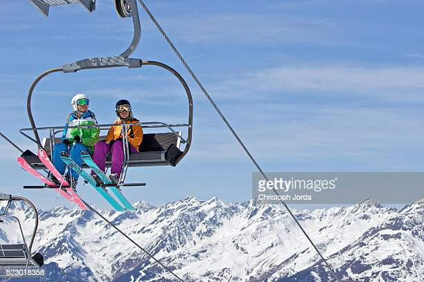 Two young female skiers sitting in ski lift
