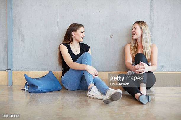 Two young female students sitting on floor chatting at higher education college