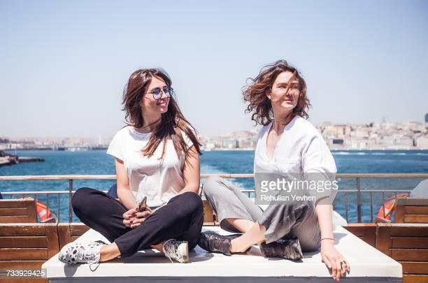 two young female tourists cross legged on passenger ferry deck, beyazit, turkey - bac photos et images de collection